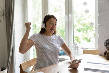 Excited millennial Caucasian female in headphones triumph win online lottery on smartphone. Happy overjoyed young woman in earphones feel euphoric read good news on cellphone. Luck concept.