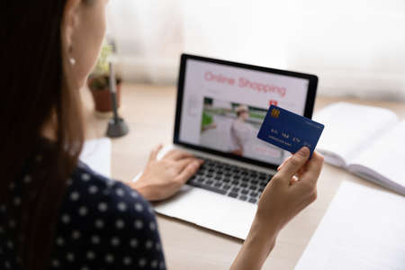 Close up back view of woman sit at desk pay with credit card shopping online on laptop from home. Female buyer or client use secure internet banking service system, make payment on web on computer.