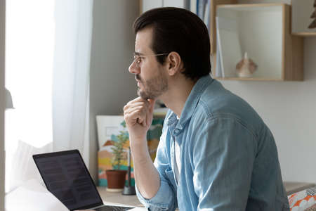 Close up of pensive young Caucasian man work on laptop at home office look in window distance thinking pondering. Thoughtful millennial male distracted from computer job planning or making decision. Stock Photo