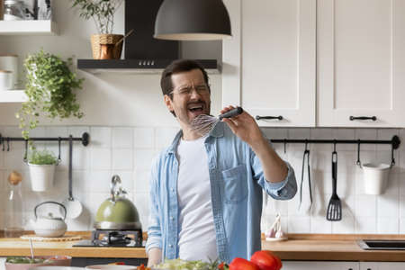 Excited funny millennial Caucasian man enjoy cooking healthy food sign in kitchen appliances in modern home. Happy young male have fun preparing delicious dinner or breakfast in the morning.
