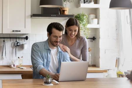 Smiling millennial couple sit at table in home kitchen using modern laptop shopping online together. Happy young Caucasian man and woman browse wireless internet on computer. Technology concept. Stock Photo