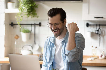 Overjoyed young Caucasian man look at computer screen feel euphoric read good news in email letter. Happy excited millennial male celebrate online lottery win on laptop. Luck, success concept. Stock Photo