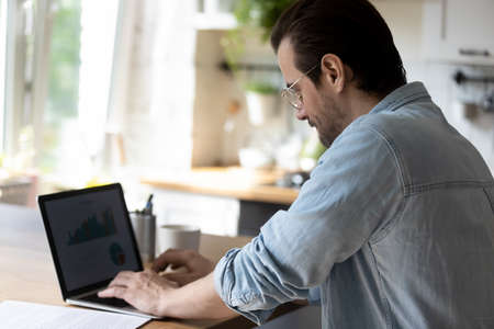 Close up of young Caucasian man sit at table at home work online on laptop with graphs and diagrams. Millennial male employee look at computer screen prepare report or research. Distant job concept.