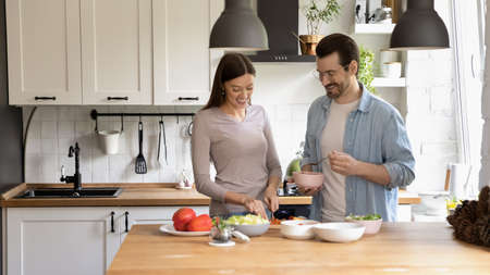 Wide banner panoramic view of happy millennial Caucasian couple cooking healthy tasty vegetarian salad in home kitchen together. Smiling young man and woman prepare delicious diet food for breakfast.
