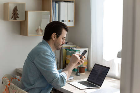 Millennial Caucasian man sit at desk at home office work on computer use modern smartphone gadget. Young male look at cellphone screen texting or messaging online. Communication, technology concept. Stock Photo