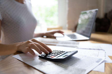 Crop close up of woman calculate on calculator manage family budget make payment on computer. Female busy take care of household expenses expenditures, paying bills on laptop online. Saving concept. Stock Photo