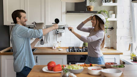 Wide banner panoramic view of happy millennial man and woman spouses have fun play with kitchen appliances cooking together. Overjoyed funny young Caucasian couple have fun enjoy morning at home.