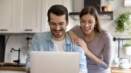 Wide banner panorama view of smiling millennial Caucasian man and woman look at laptop screen win lottery online. Happy young couple feel overjoyed read good news or amazing discount deal on computer.