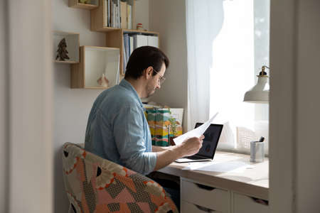 Back candid view of millennial Caucasian man sit at desk at home office working distant on laptop with paperwork. Young male look at computer screen study online on gadget with paper documents.