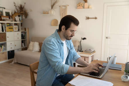 Serious millennial Caucasian man sit at table at home office look at laptop screen working online on gadget. Pensive focused young male type text consult client distant on computer. Freelance concept.