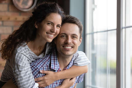 Head shot portrait smiling husband piggy backing beautiful wife, having fun, overjoyed young couple hugging, looking at camera, enjoying leisure time at home together, romantic relationship