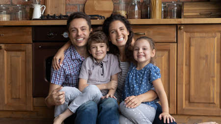 Portrait overjoyed parents with kids sitting on warm kitchen floor, hugging, looking at camera, smiling father and mother hugging little daughter and son, posing for photo at home, mortgage
