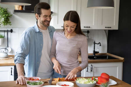 Happy millennial Caucasian man and woman spouses have fun cooking healthy diet salad for dinner. Smiling young couple renters enjoy morning at home preparing delicious vegetarian food together.