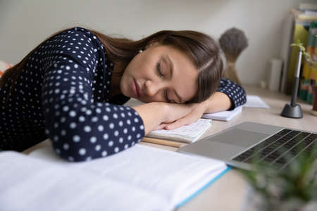Exhausted millennial Caucasian female student fall asleep or doze on desk studying on computer at home. Tired young woman sleep relax on notebooks books, overwhelmed with work. Fatigue concept.