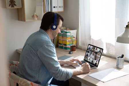 Smiling Caucasian man in headphones sit at desk at home office talk on video call on computer with diverse businesspeople. Young male in earphones have webcam digital virtual meeting with colleagues.