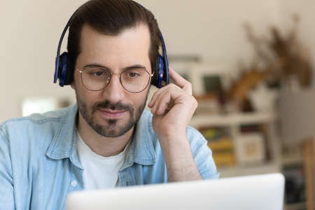 Close up of millennial male in headphones and glasses look at laptop screen watch webinar online. Young Caucasian man in earphones talk speak on video call on computer, have webcam digital conference. Stock Photo