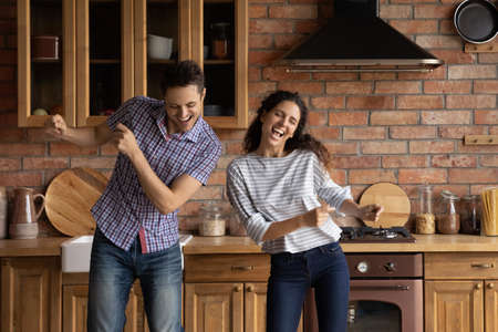 Overjoyed young couple dancing in modern kitchen, having fun, moving to music, listening to favorite song, enjoying leisure time, satisfied family excited by relocation in new own apartment Stock Photo
