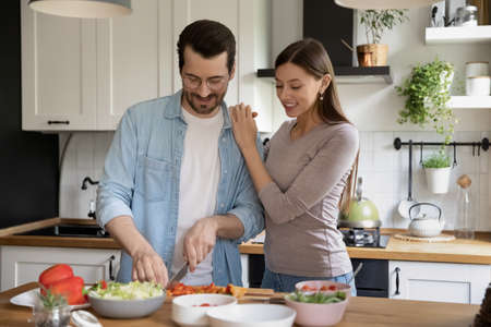 Happy millennial man and woman spouses prepare healthy tasty vegetarian salad for dinner in home kitchen together. Smiling young Caucasian couple renters have fun cooking delicious diet food indoors.