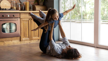Caring mother holding little daughter pretending flying with hands outstretched, lying on warm wooden floor in kitchen, loving young mum carrying adorable girl, family engaged in funny activity