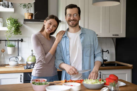 Portrait of happy young family pose in modern cozy home kitchen preparing healthy vegetarian salad. Smiling millennial couple renters cooking delicious diet food in the morning in own modern house.