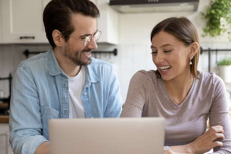 Overjoyed millennial man and woman look at laptop screen have fun using gadget at home together. Smiling young Caucasian couple laugh shopping online on computer. Technology, communication concept. Stock Photo