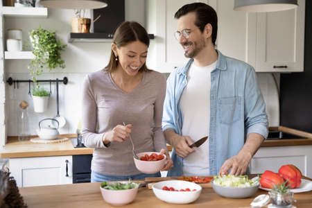 Overjoyed millennial man and woman have fun cooking healthy tasty vegetarian salad in kitchen together. Smiling young Caucasian couple prepare delicious vegetable diet food in own cozy house.