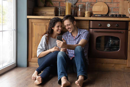 Happy young couple using phone, sitting on warm wooden kitchen floor, enjoying leisure time together, smiling man and woman looking at screen, shopping, browsing apps, watching funny video Stock Photo