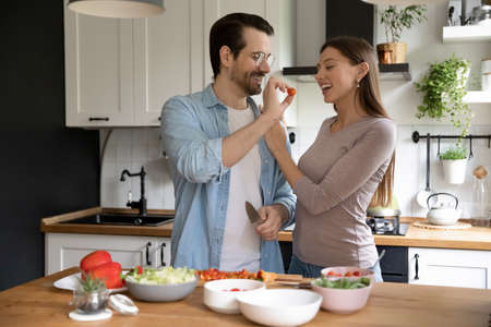 Overjoyed young couple have fun cooking healthy vegetarian diet salad enjoy morning in cozy home kitchen. Happy millennial Caucasian woman and man spouses prepare delicious food in own modern house. Stock Photo