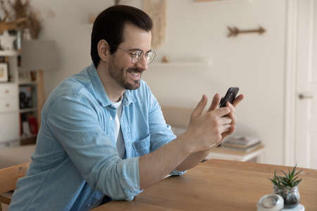 Smiling young man sit at table at home look at smartphone screen browse wireless internet on gadget. Happy millennial Caucasian male use cellphone text message online on device. Technology concept.