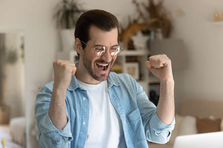Close up of overjoyed millennial Caucasian man feel euphoric read good news or get promotion email on laptop. Excited young male triumph with online lottery win or victory on computer. Luck concept.