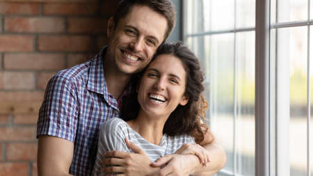 Head shot portrait overjoyed happy young couple hugging, standing at home, smiling husband embracing beautiful wife from back, looking at camera, enjoying tender moment, posing for family photo Stock Photo