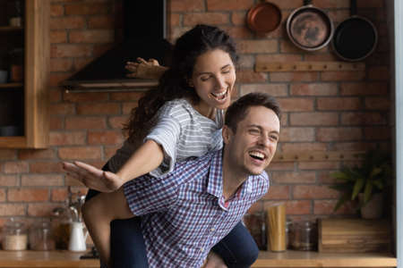 Overjoyed husband piggy backing laughing beautiful wife pretending flying with hands outstretched close up, family having fun at home together, excited young couple celebrating relocation, mortgage