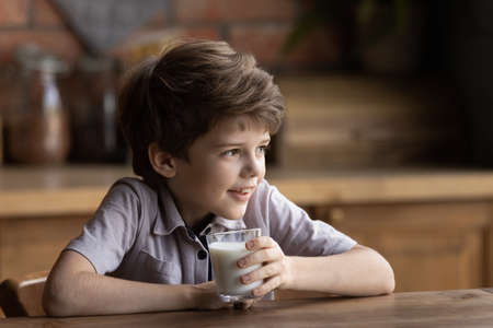 Close up smiling little boy holding glass of milk, sitting at wooden table in kitchen, adorable child kid enjoying organic food yogurt, getting vitamins and calcium, children healthcare concept
