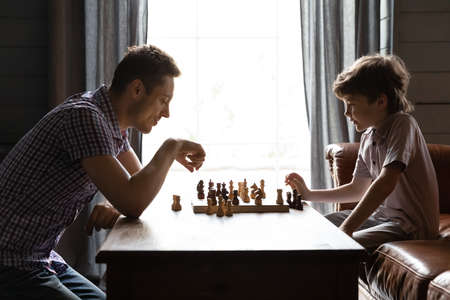 Side view father and adorable little son playing chess at home, having fun, spending leisure time together, caring dad or babysitter teaching preschool boy, family engaged in board game, competition