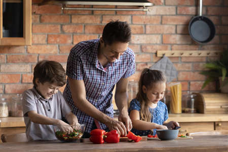 Smiling father with little son and daughter cooking salad together, standing at wooden table in kitchen, adorable boy and girl cutting vegetables, family having fun, preparing meal, enjoying leisure