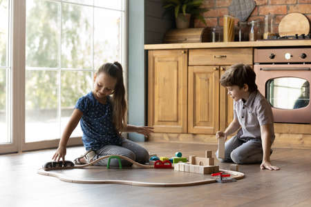 Two little kids playing with toys, bricks and train, building tower and railway, sitting on warm wooden floor with underfloor heating at home, preschool sister and brother having fun together Stock Photo