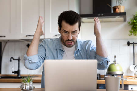 Unhappy mad millennial man look at laptop screen shocked by online virus or spam on web on gadget. Angry young Caucasian male user frustrated confused by computer operational problem or malfunction.