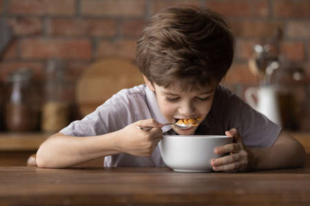 Close up happy cute little boy eating sweet tasty delicious corn cereals with milk, sitting at wooden table in kitchen, hungry adorable child kid enjoying breakfast in morning, holding spoon