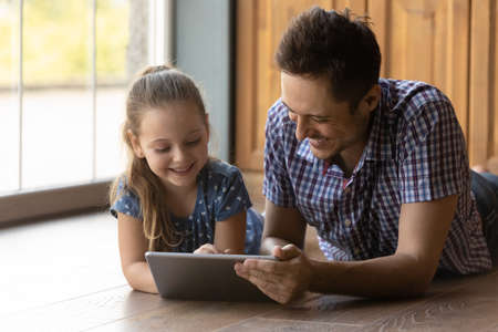 Caring father and little daughter having fun with tablet together, lying on warm floor with underfloor heating, smiling dad with adorable child browsing apps, playing game, watching video at home Stock Photo
