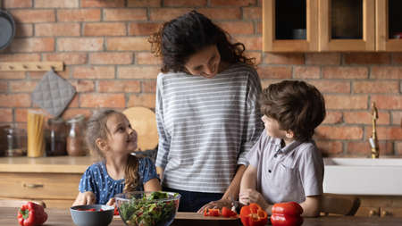 Happy mother with little son and daughter cooking salad together, standing at table in modern kitchen, preschool girl and boy cutting fresh vegetables, family having fun, enjoying leisure time