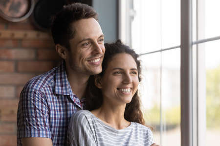 Close up smiling man and woman hugging, looking out window, standing at home, happy dreamy young couple visualizing future together, excited wife and husband planning, dreaming and thinking