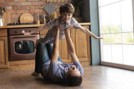 Portrait little boy pretending flying, playing fanny game with father, caring loving young dad holding lifting son, lying on warm wooden floor in kitchen, family spending leisure time at home