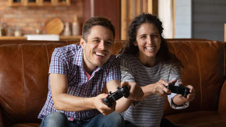 Close up overjoyed young couple playing video game together, having fun with console, smiling laughing young man and woman sitting on couch at home, holding remote controllers, enjoying leisure time