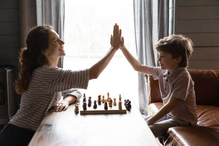 Side view smiling mother and little son playing chess, teacher and student giving high five, celebrating win, successful game result, family involved in board game activity, having fun at home
