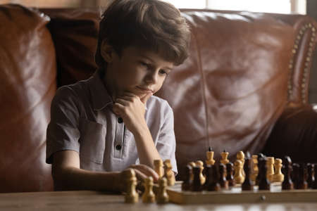 Close up thoughtful little boy playing board game, chess, touching chin, sitting on couch at home, pensive child looking at board, pondering developing win strategy, making decision