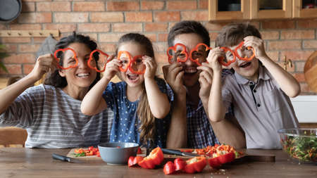 Funny portrait happy family holding red pepper circles as glasses, looking at camera, sitting at table in kitchen, smiling mother and father with kids posing for funny photo at home, cooking together