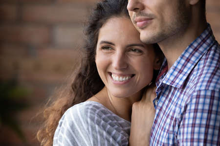 Close up smiling beautiful dreamy woman hugging man, looking to aside, happy young wife visualizing good future with husband, young couple enjoying tender moment, planning, standing at home Stock Photo