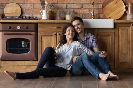 Portrait smiling man and woman sitting on warm wooden floor in kitchen, happy young couple looking at camera, posing for photo, family relaxing in first own apartment, excited by relocation