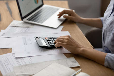 Crop close up of Caucasian woman sit at desk calculate expenses on calculator paying on laptop online. Female busy manage family budget account expenditures, use computer for financial operations.