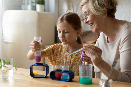 Engaging science. Attentive old grandma assist grandkid in funny scientific research using chemical set for children. Mature woman tutor teach small girl chemistry in game mix colored reagents in bulb